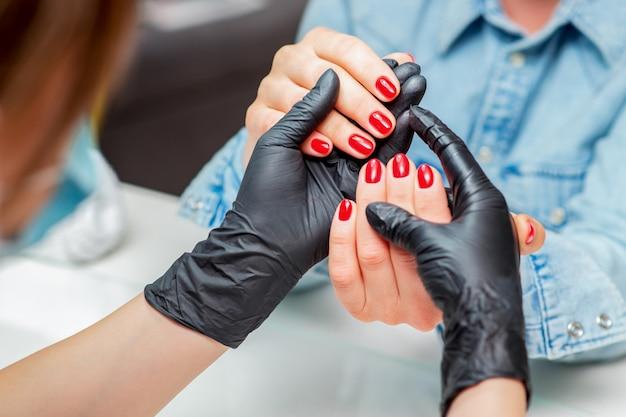 Manikiurzystka trzyma ręce z czerwonymi paznokciami kobieta klienta z bliska.