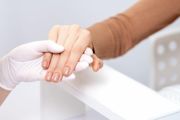 Manikiurzystka trzymając rękę kobiety z beżowym manicure z bliska.