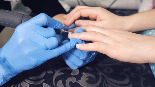 Manikiurzystka wykonuje zabieg regeneracji i przedłużania paznokci na paznokciach dziewczyny w salonie paznokci.