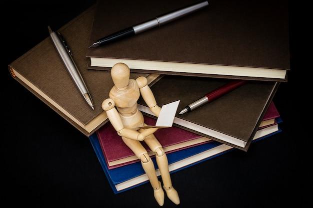 Maniqui czytanie siedzi na górze książek i długopisów