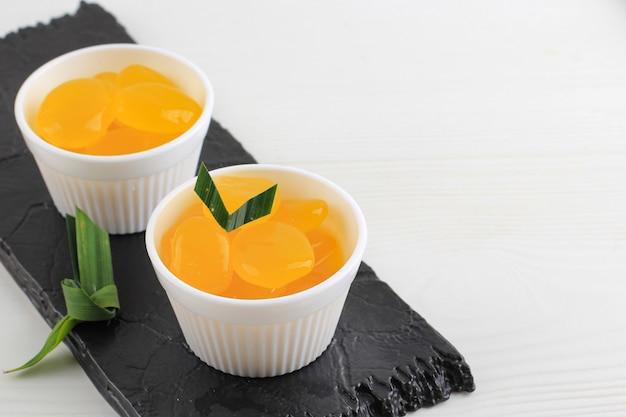 Manisan kolang-kaling lub konserwowany owoc palmy cukrowej, zabarwiony na żółto, tradycyjne indonezyjskie typowe orzeźwienie i deser podczas miesiąca ramadan oraz w idul fitri lub hari raya.