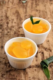 Manisan kolang-kaling (zakonserwowany owoc palmy cukrowej) z żółtym kolorem. serwowany w białej misce ten deser to typowe indonezyjskie orzeźwienie oraz podczas ramadanu i idul fitri lub hari raya.