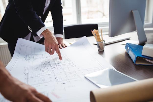 Manle projektant wnętrz omawiający plan ze współpracownikiem