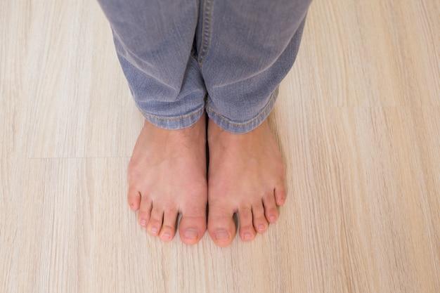 Mans bosymi stopami na drewnianej podłodze
