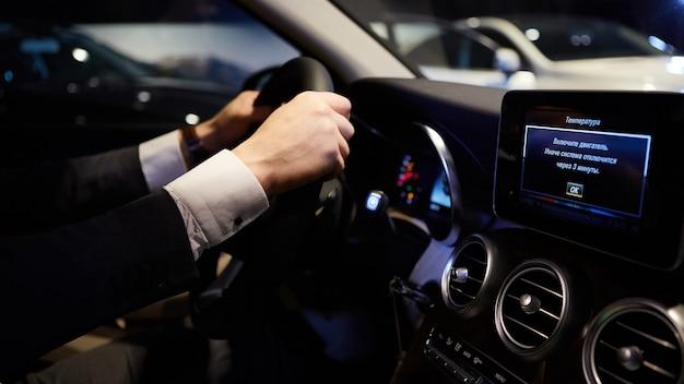 Mans duże dłonie na kierownicy podczas prowadzenia samochodu