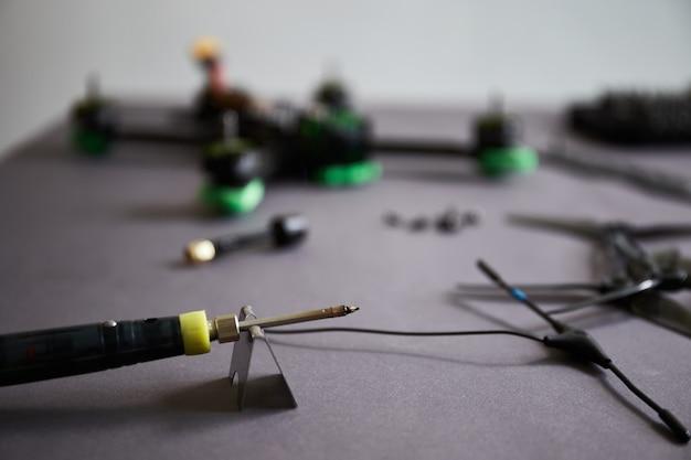 Mans ręce montujące drona za pomocą narzędzi przygotowujących szybki quadkopter wyścigowy do lotu