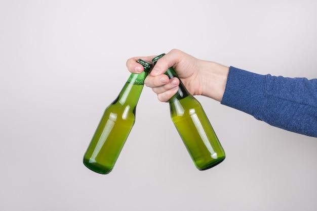 Mans ręka trzyma dwie przezroczyste butelki z płynem na białym tle