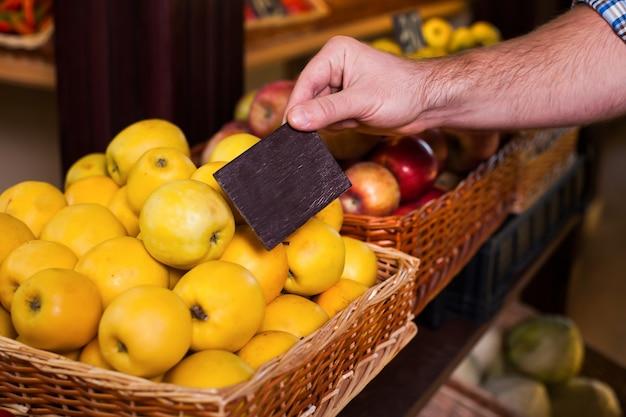 Mans ręka trzyma metkę z ceną na dojrzałych jabłkach.