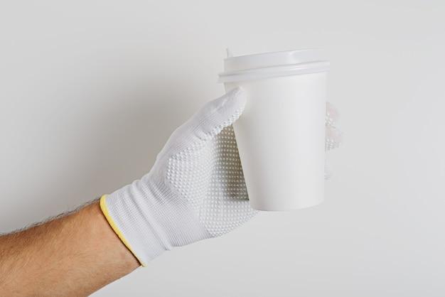 Mans ręka w białej rękawiczce trzymając biały papierowy kubek na białym tle