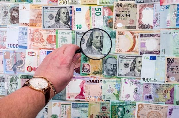 Mans ręka z lupą sprawdzającą kolekcję banknotów