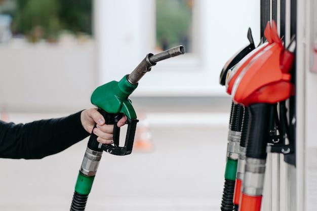 Mans ręka za pomocą dyszy paliwowej na stacji benzynowej