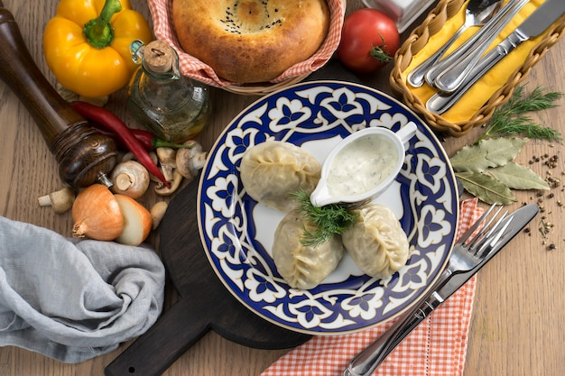 Manti z jagnięciną, kwaśną śmietaną i koperkiem w talerzu z tradycyjnym uzbeckim