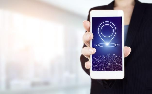 Mapa gps, lokalizacja adresu pin w aplikacjach mobilnych. ręka trzymać biały smartphone z cyfrowym hologramem znak lokalizacji znak na jasnym tle niewyraźne.