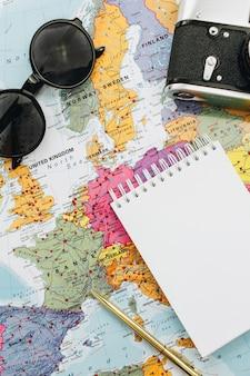 Mapa świata, aparat, okulary przeciwsłoneczne i notatnik