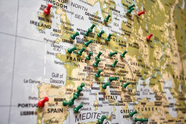 Mapa świata z inną pinezką w krajach, w których podróżowali traveltopography i kolorowe tło koncepcji turystycznej