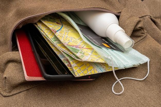 Mapa turystyczna, karta kredytowa, paszport, środek dezynfekujący, maska ochronna w kieszeni plecaka podróżnego