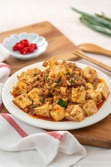 Mapo tofu, smażone tofu z ostrym ostrym sosem na białym talerzu, słynna chińska kuchnia dla smakoszy.