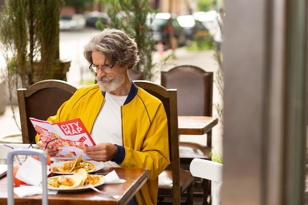 Mapowanie trasy. skoncentrowany mężczyzna siedzący w ulicznej kawiarni podczas lunchu przyglądający się uważnie mapie miasta przed spacerem.