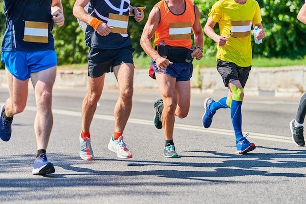 Maratończycy na miejskiej drodze. zawody w bieganiu. sprint uliczny na świeżym powietrzu