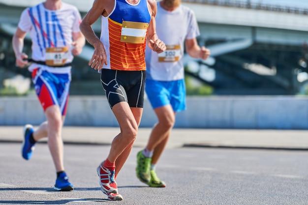 Maratończycy na miejskiej drodze. zawody w bieganiu.