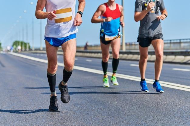 Maratończycy na miejskiej drodze. zawody w bieganiu