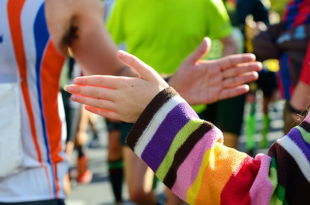 Maratonowy wyścig biegowy wspierający biegaczy na drodze dziecka, dający koncepcję sportu przybijającego piątkę