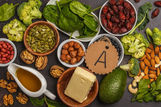 Marchew, orzechy, brokuły, masło, ser, awokado, morele, nasiona, jaja. ciemne tło, widok z góry