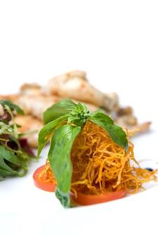 Marchewka i pomidor z zielonymi liśćmi