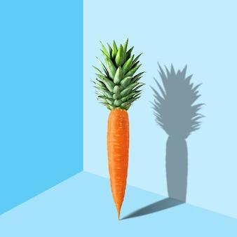 Marchewka z liśćmi ananasa na pastelowo błękitnej powierzchni.
