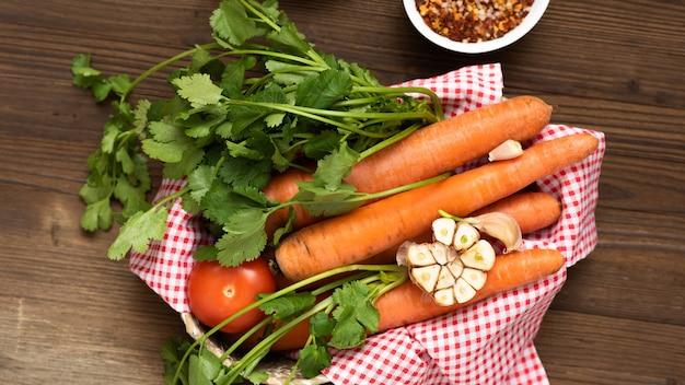 Marchewki z ziołami w wiklinowym koszu z przyprawami.