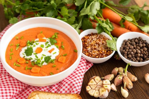 Marchewkowa zupa ze świeżo zmielonej marchewki z ziołami i śmietaną na drewnianej powierzchni.