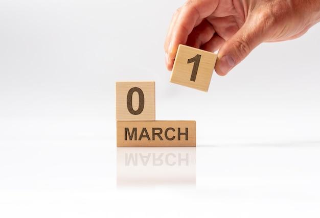 Marcowy napis na drewnianym kalendarzu. witaj wiosno.