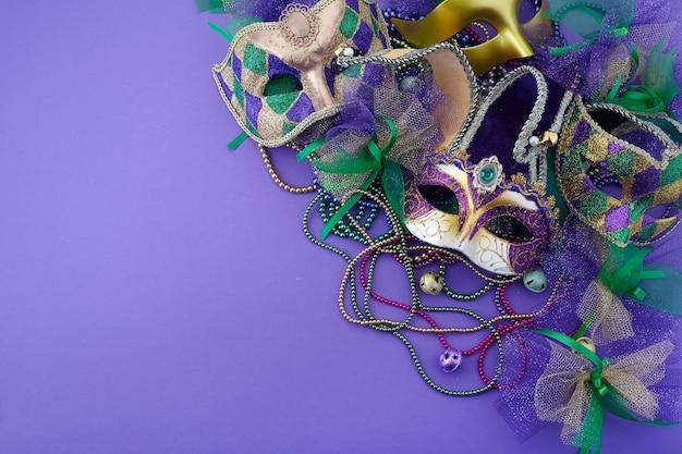 Mardi gras, maska wenecka lub karnawałowa na fioletowym tle z miejscem na tekst. widok z góry