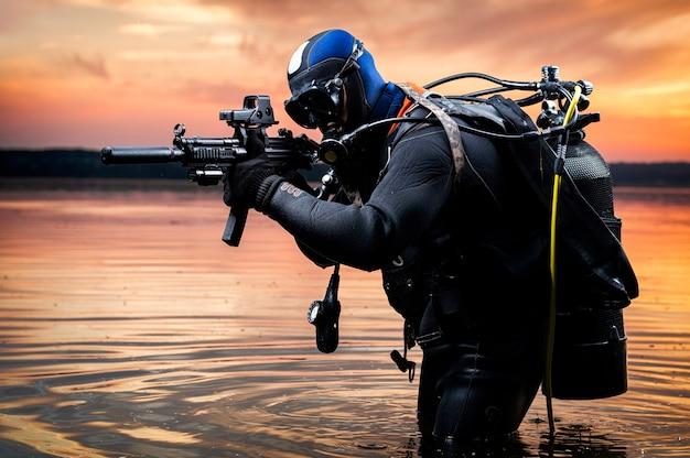 Marine wychodzi z wody i zbliża się do celu z bronią w ręku. pojęcie gier wideo, reklamy, niestabilności na świecie, konfliktów państwowych. różne środki przekazu