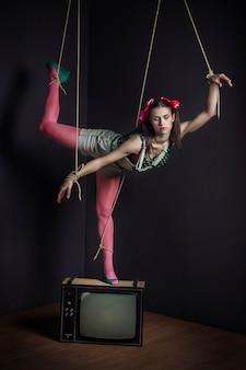Marionetka kobieta w telewizji z przywiązanymi rękami pozowanie