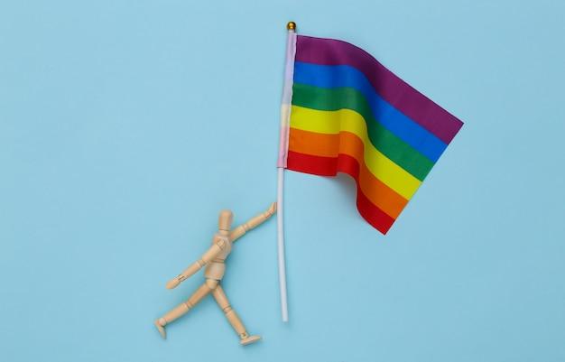 Marionetka wodden trzyma tęczowa flaga lgbt na żółtym tle. tolerancja, wolność, parada gejów