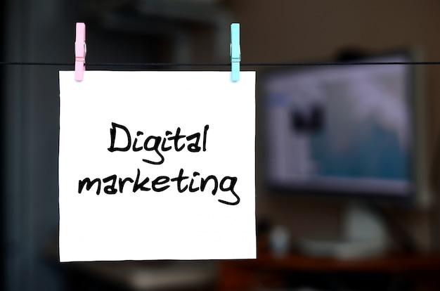 Marketing cyfrowy. uwaga jest napisana na białej naklejce, która wisi za pomocą spinacza