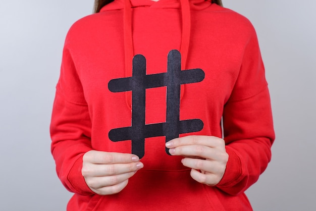 Marketing internetowy koncepcja sprzedaży tweet dla młodzieży. przycięte zbliżenie zdjęcie wesoły pozytywny zadowolony optymistyczny uśmiech toothy młodzieniec trzymający duży duży czarny hashtag w dłoni na białym tle szarym