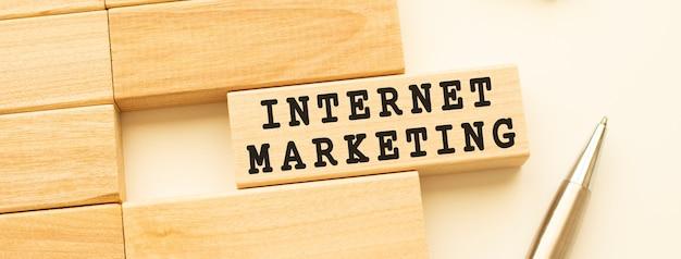 Marketing internetowy tekst na drewnianym pasku leżącym na białym stole z metalowym długopisem. pojęcie.