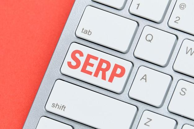 Marketingowe hasło serp. strona wyników wyszukiwarki terminów na klawiaturze.