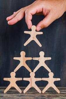 Marketingowy pojęcie na drewnianego i ciemnego tła bocznym widoku. ręcznie budować stos drewnianych figur.