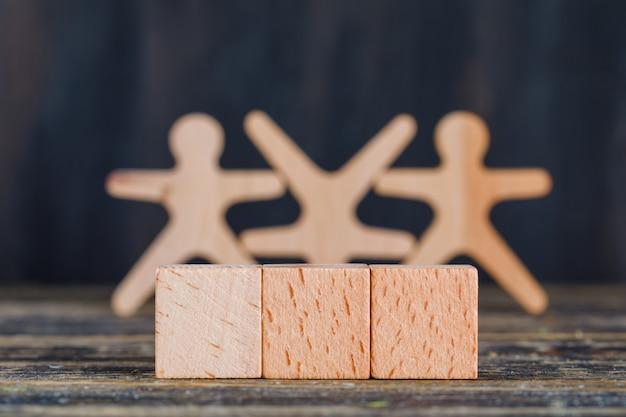 Marketingowy pojęcie z drewnianymi postaciami, sześcianami na drewnianym i grunge tła bocznym widoku.