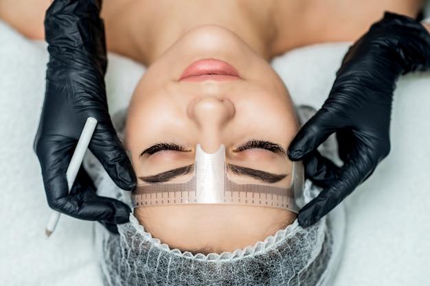 Markup z linijką na brwiach młodej kobiety podczas makijażu permanentnego.