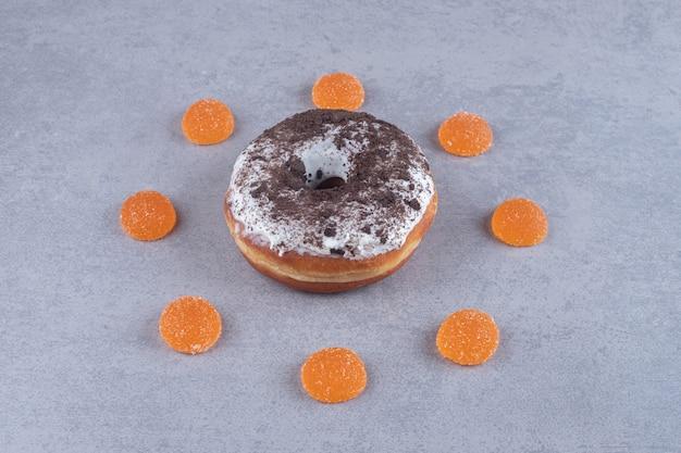Marmelowy pierścień wokół pączka na marmurowej powierzchni