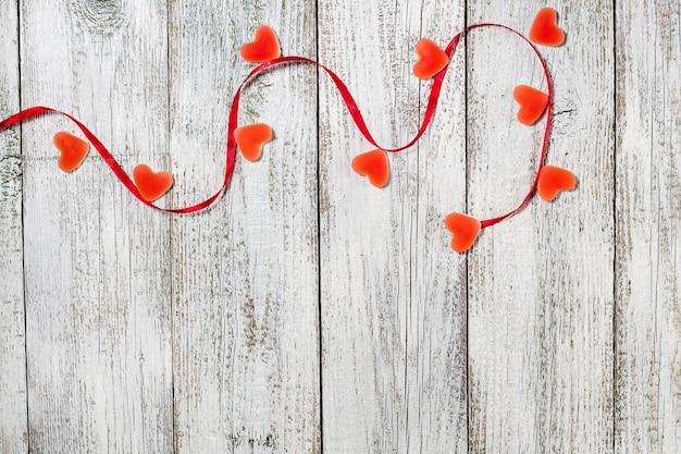 Marmolada w kształcie serca i czerwoną wstążką na drewnianym stole, kompozycja walentynkowa, kartka z życzeniami.