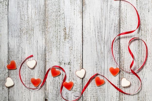 Marmolada w kształcie serca w kształcie cukierków i czerwona wstążka na drewnianym stole, kompozycja walentynkowa, kartka z życzeniami
