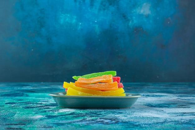 Marmolada w postaci kolorowych patyczków w talerzu, na niebieskim stole.