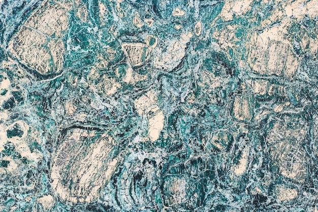 Marmurowa faktura kamienia o zróżnicowanym wzorze z drobnymi liniami.