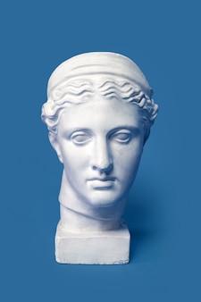 Marmurowa głowa młodej kobiety, popiersie starożytnej greckiej bogini na białym tle. Gipsowa kopia posągu głowy Diany