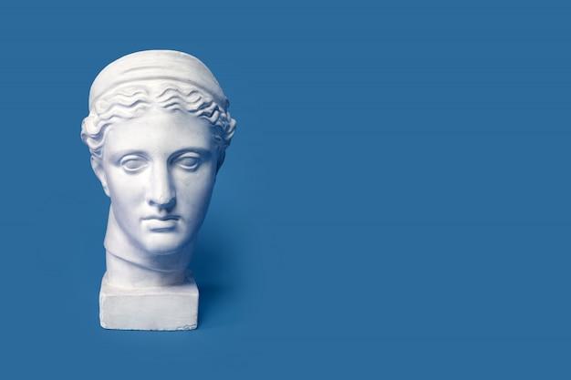 Marmurowa głowa młodej kobiety, popiersie starożytnej greckiej bogini na białym tle na niebieskim tle. gipsowa kopia posągu głowy diany